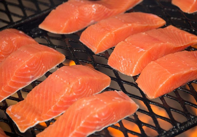 Photo of Fresh salmon grilling over an open fire