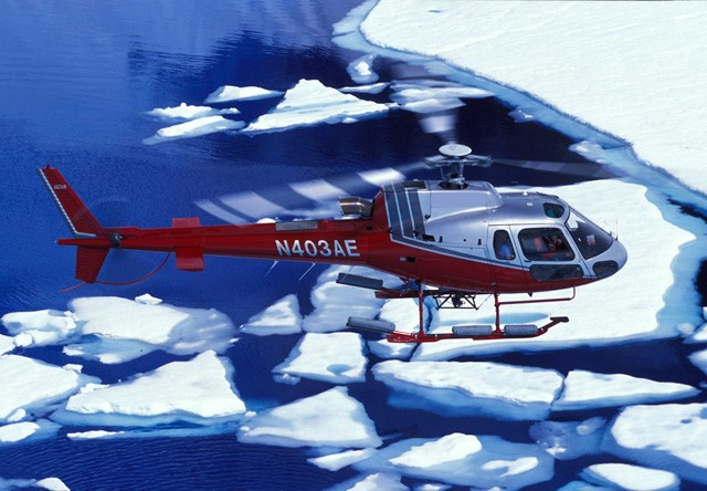 helicopter flying over glacier
